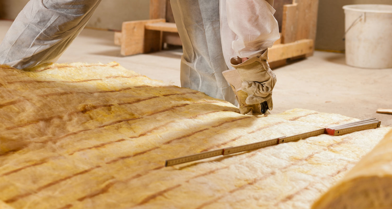A worker installs sound-absorbing insulation.