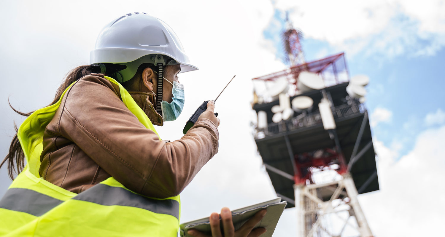 A construction worker wearing a facemask uses a radio to communicate with another worker.