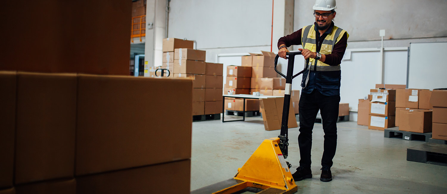 A construction worker follows proper safety precautions before using a pallet jack.