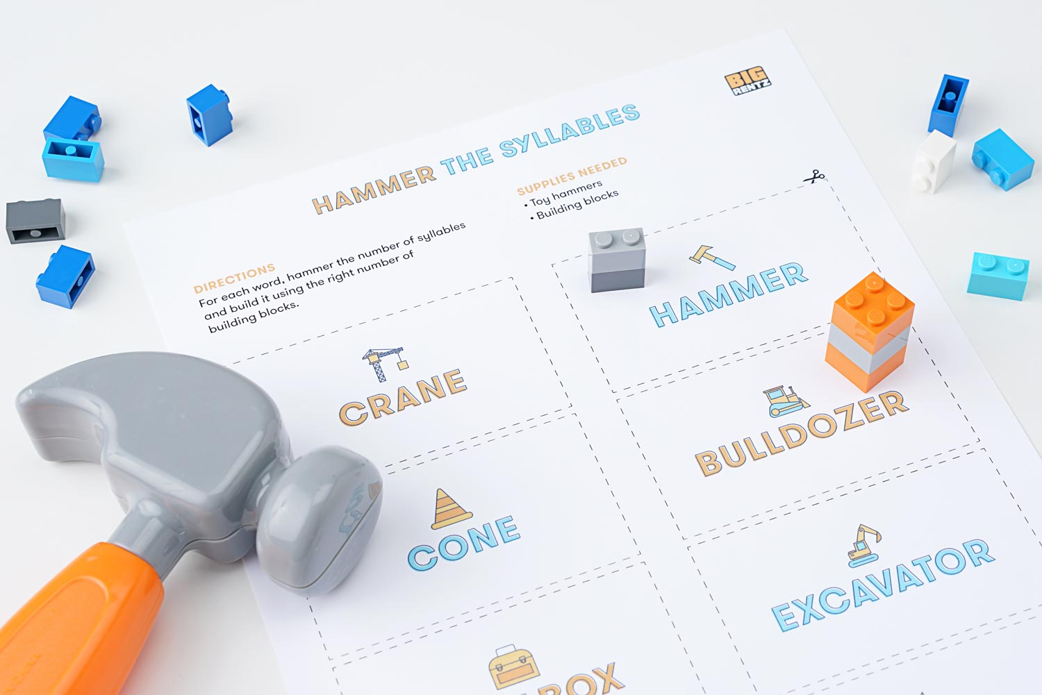 Language game featuring words, a toy hammer, and building blocks