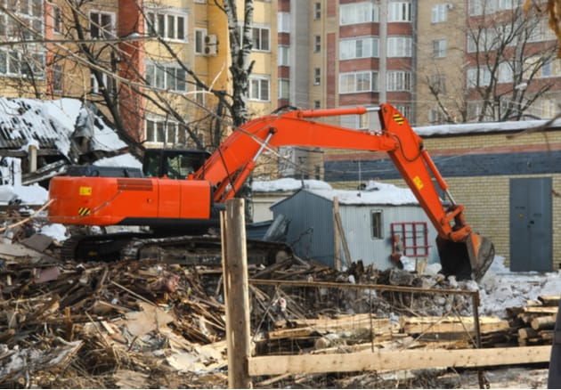excavator scooping snow and debris