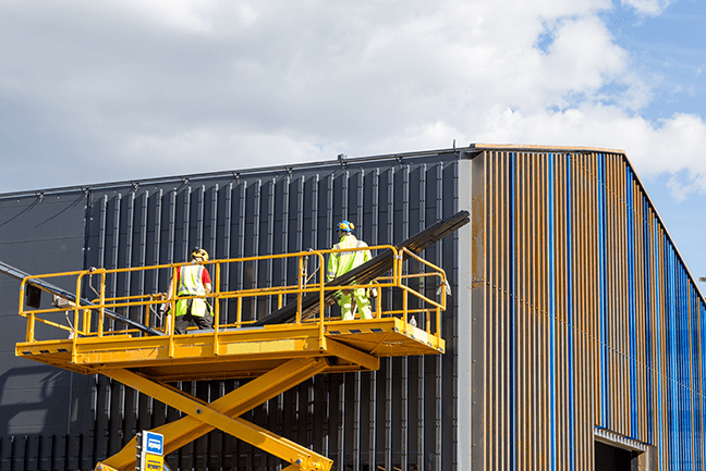 two men working on a yellow scissor lift on the outside of a building