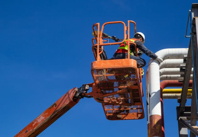 orange boom lift with a man in the basket working on a white pipe in the air