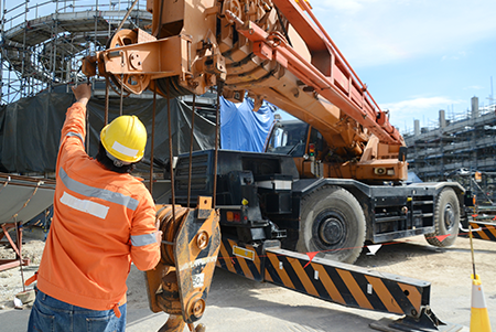 man next to a crane with on a jobsite