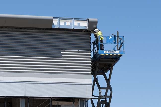 man on blue scissor lift raised up working on the top corner of a tall building