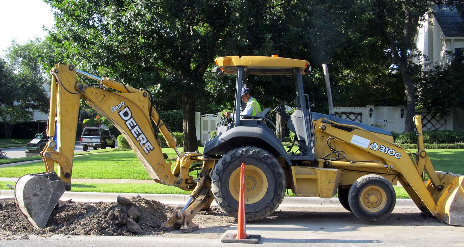 backhoe in a neighborhood digging a hole