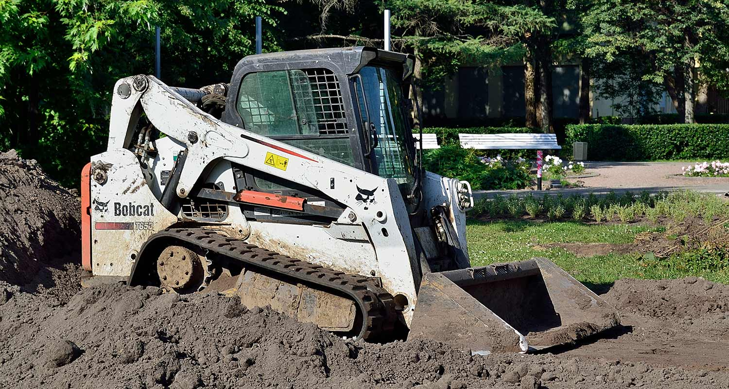 a compact track loader in dirt
