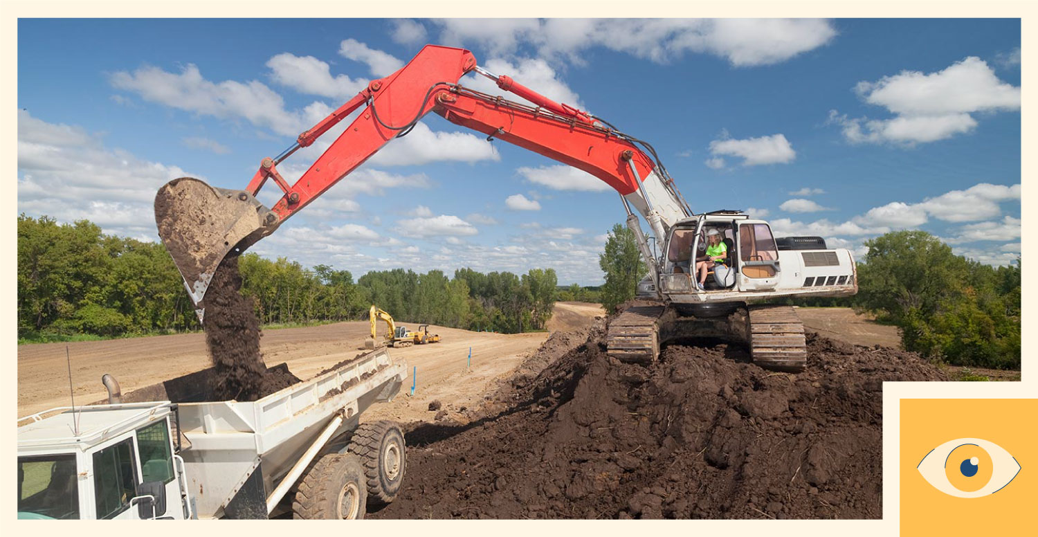 A construction worker operates an excavator.