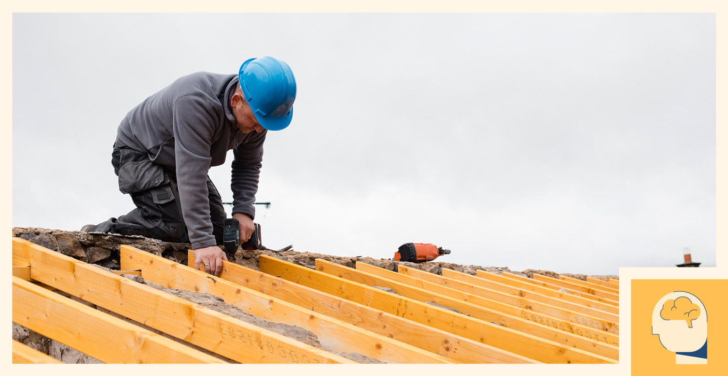 A construction draws on his knowledge of roofing and installs wood components.