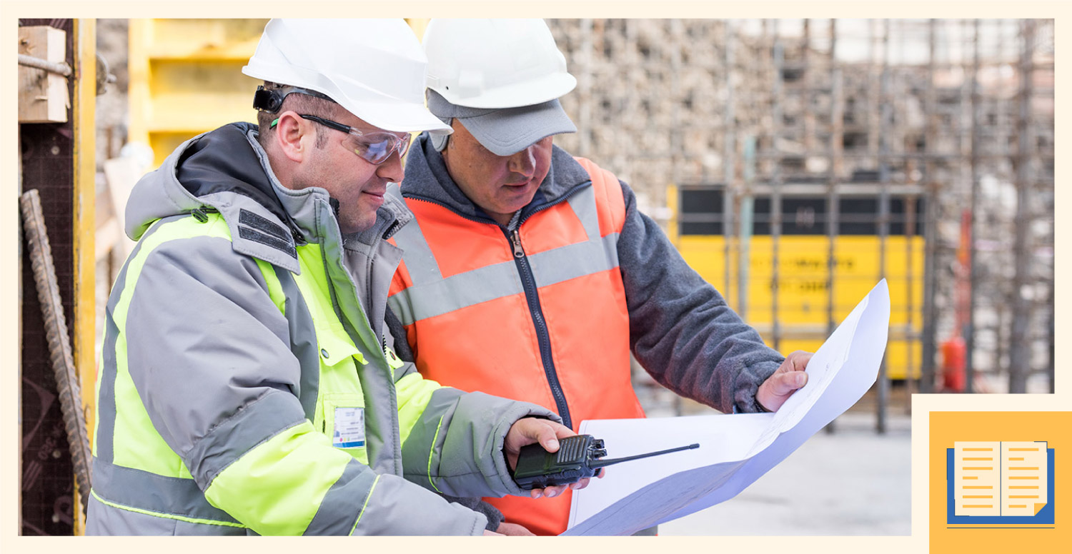 Two construction workers read and analyze a blueprint.
