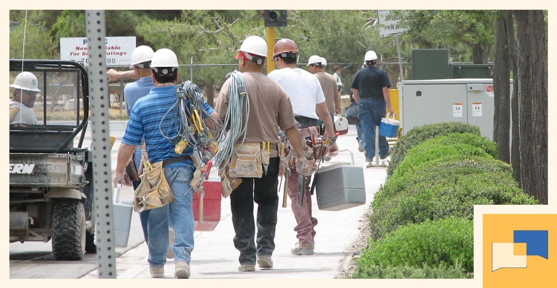 construction workers walking away on a sidewalk