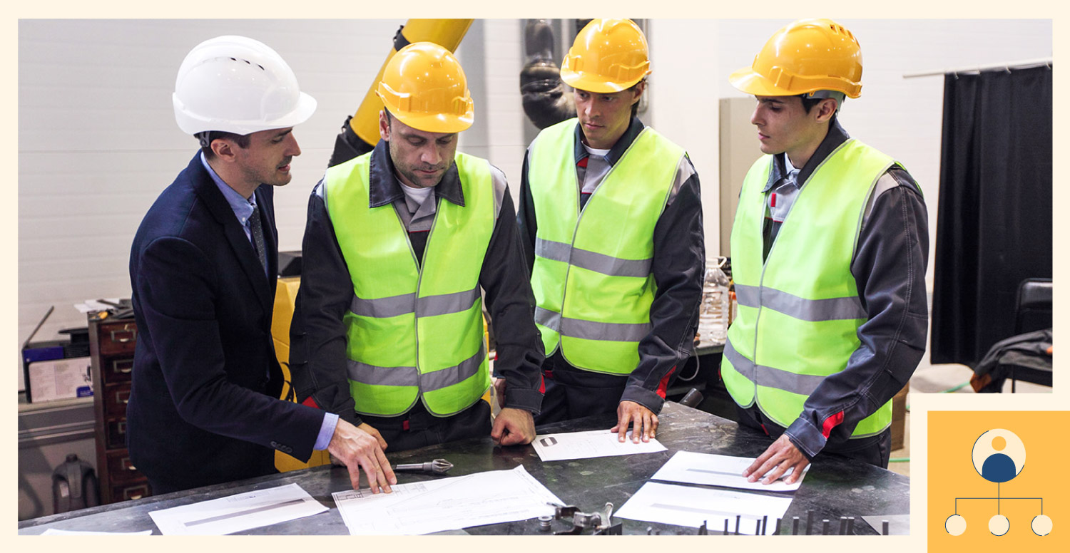 Construction workers meeting with boss to discuss plans for a project