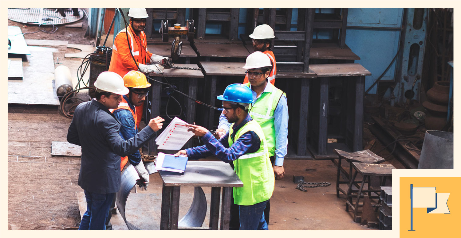 A construction manager leads a discussion with the contractors and employees.