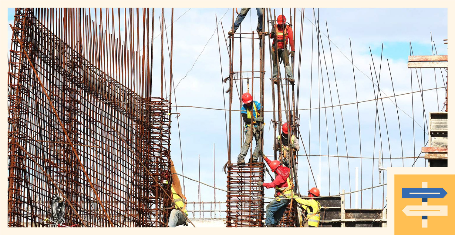 A group of construction workers working on a building frame.