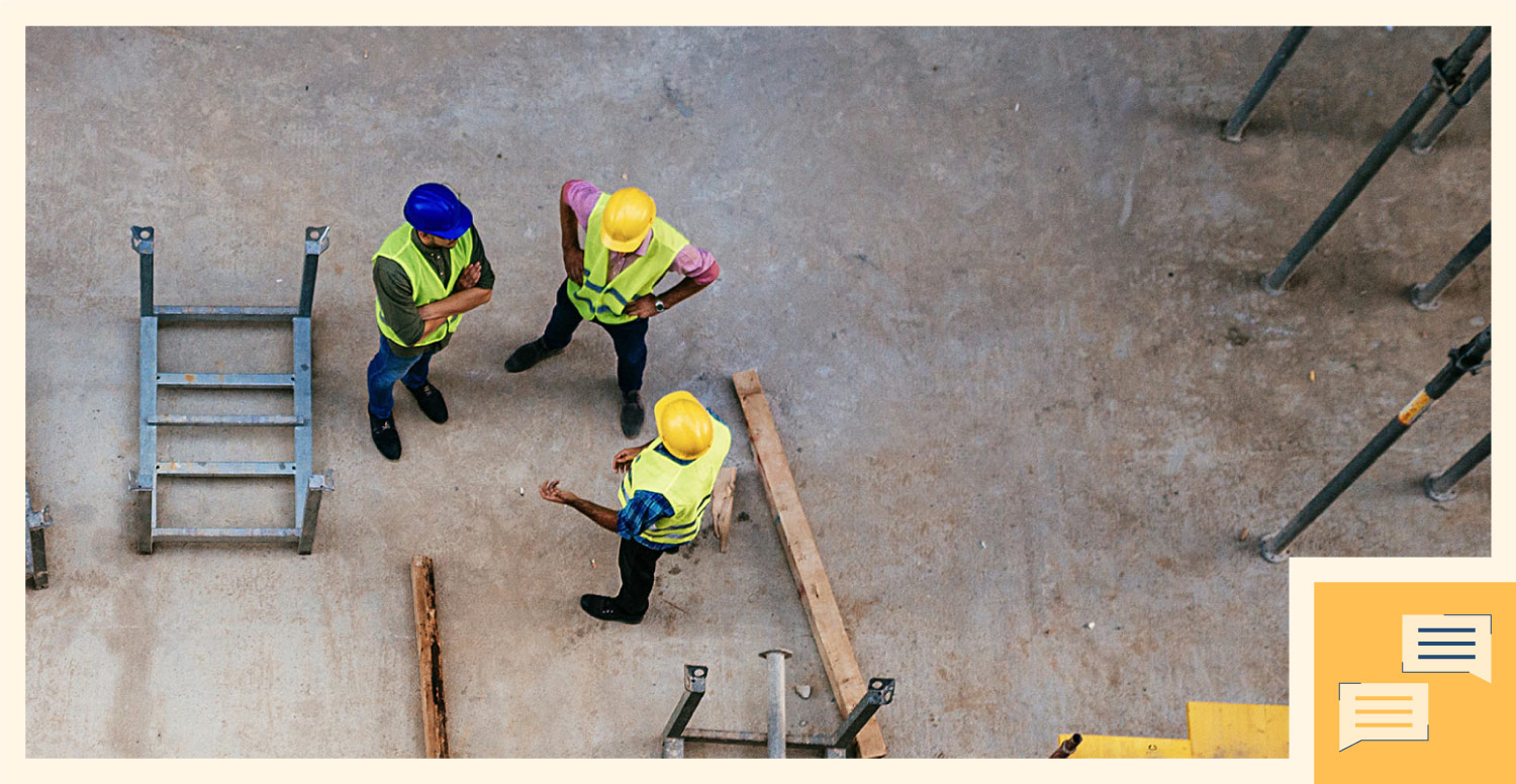Three construction workers talk and communicate about their project on a worksite.