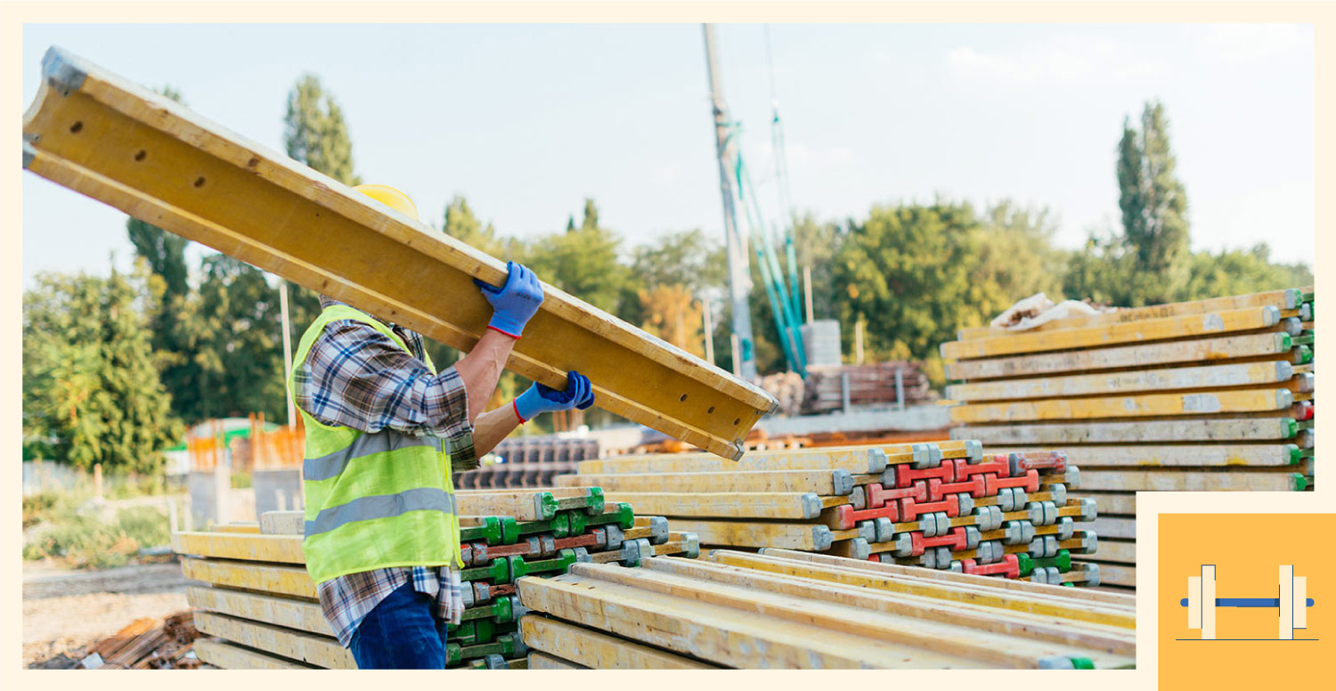 A construction worker uses his strength to lift up a beam.