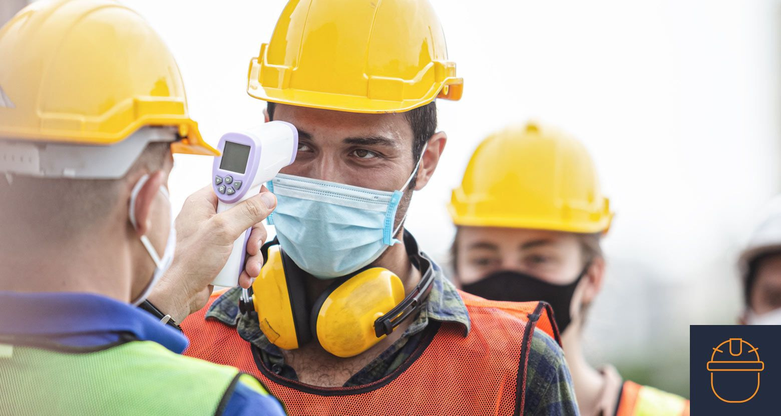 a masked construction worker has their temperature checked