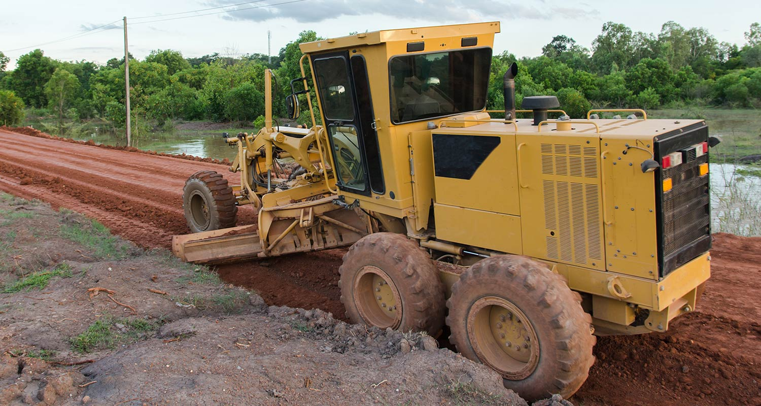 a motor grader in a ditch