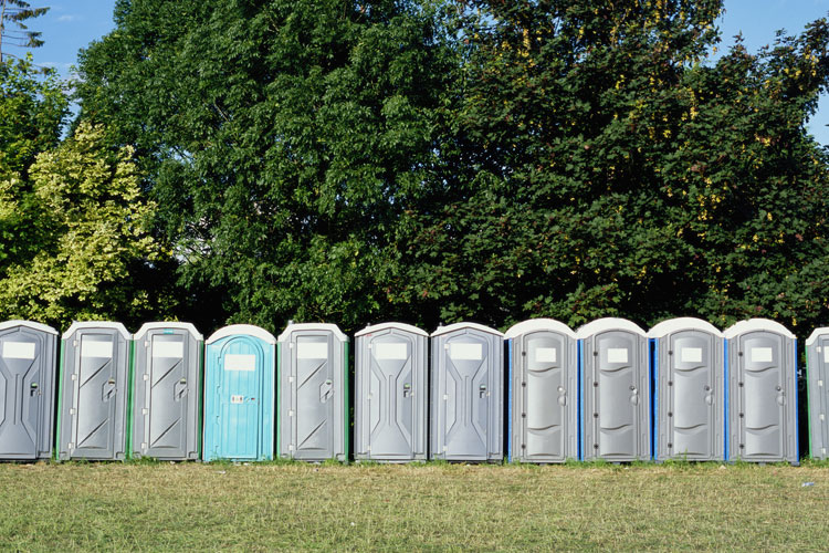 A line of porta potties in a outdoor field