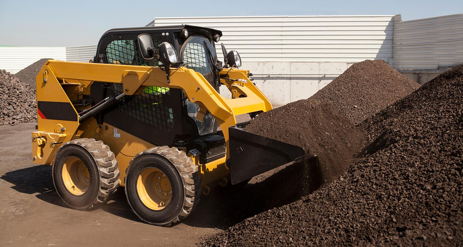 a skid steer loader picking up dirt