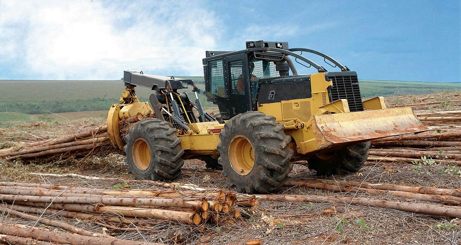 a skidder next to a pile logs